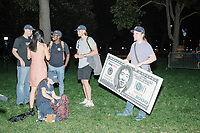"""A man holds a giant $1000 bill featuring a portrait entrepreneur and Democratic presidential candidate Andrew Yang after the candidate spoke to a large crowd in Cambridge Common near Harvard Square in Cambridge, Massachusetts, on Mon., September 16, 2019. Yang's unlikely presidential bid is centered on his idea for a """"Freedom dividend,"""" which would give USD$1000 per month to every adult in the United States. After appearing in three Democratic party debates, Yang has risen in polls from longshot candidate to within the top 10."""