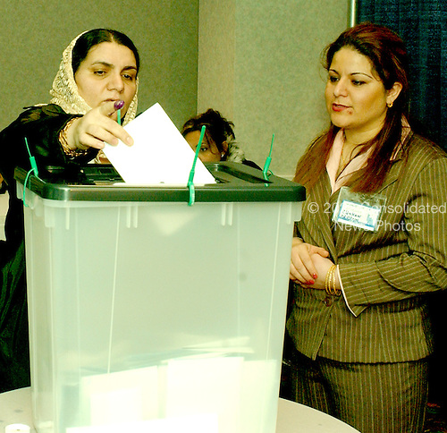 McLean, VA - December 13, 2005 -- Fatima Youssif, left, who emigrated to Binghamton, New York from Duhua, Iraq to escape being gassed by Saddam Hussein, casts her ballot under the watchful eye of an unidentified poll worker, right, in the Iraqi election in McLean, Virginia on December 13, 2005. .Credit: Ron Sachs / CNP.(RESTRICTION: NO New York or New Jersey Newspapers or newspapers within a 75 mile radius of New York City)