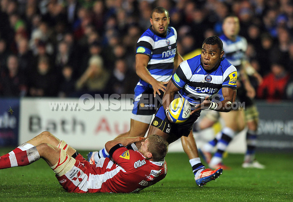 Semesa Rokoduguni looks to offload the ball after being tackled. Aviva Premiership match, between Bath Rugby and Gloucester Rugby on October 25, 2013 at the Recreation Ground in Bath, England. Photo by: Patrick Khachfe / Onside Images