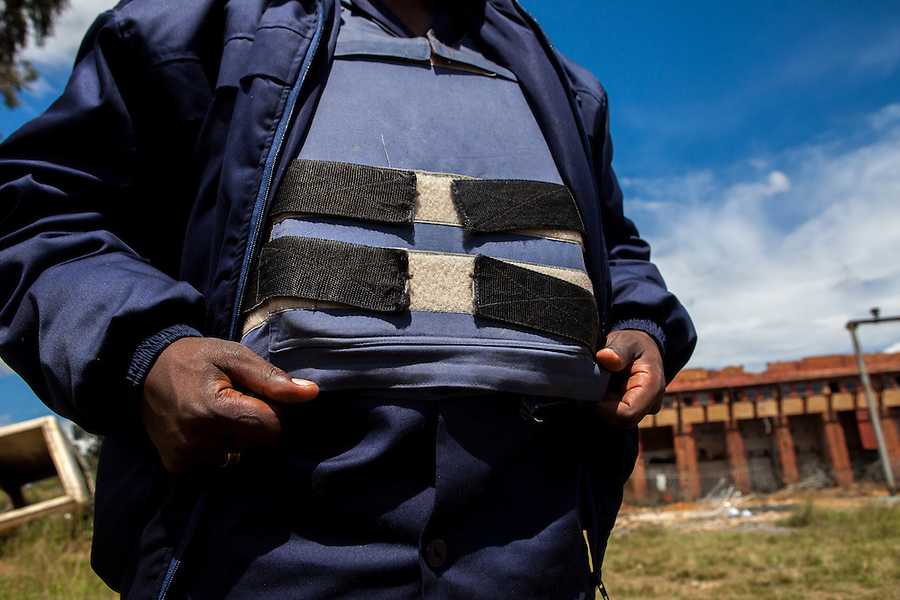 A security guard wears a bullet proof vest as he stands on duty outside abandoned gold mine, Durban Deep's substation. Days before, the entire substation was ransacked and the cables and transformers were stolen, leaving the neighborhood without power.
