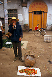 China 1990s. Liufu village a rural community Anhui Province man selling home grown food in the daily market. 1998