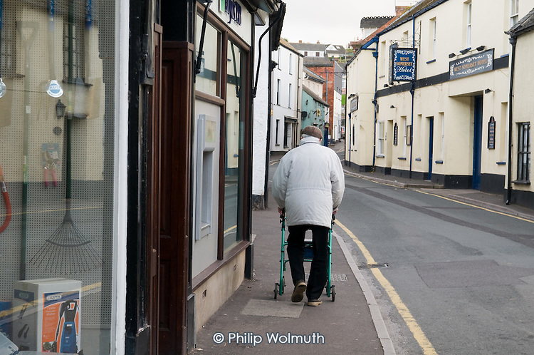Elderly man with a walking frame in the village of Watchet, Somerset.