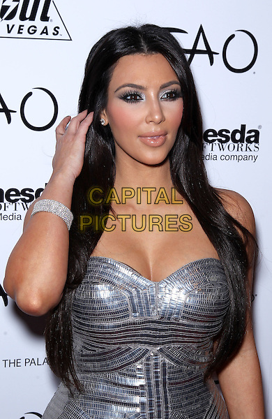 "KIM KARDASHIAN.Kim Kardashian celebrates her 30th birthday with ""Fallout: New Vegas"" at Tao Nightclub inside the Venetian Resort Hotel and Casino, Las Vegas, Nevada, USA, 15th October 2010..half length strapless silver dress hand touching hair cleavage patterned bracelet  make-up shiny eyelashes .CAP/ADM/MJT.© MJT/AdMedia/Capital Pictures."