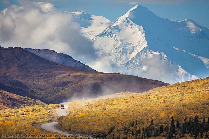 A tour bus travels the Denali Park road in autumn with Denali in the distance, Denali National Park, Interior, Alaska.