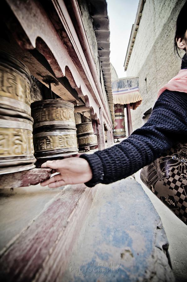 Ladakhi women spinning prayer wheels, Shey Palace, Naropa Royal Palace, in Ladakh, India.