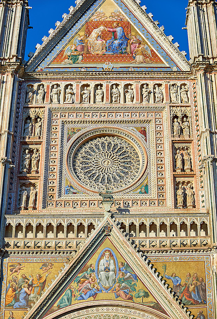 Close up of a gable with mosaics depicting the the Virgin Mary created between 1350 and 1390 after designs by artist Cesare Nebbia and the rose window built by the sculptor and architect Orcagna between 1354 and 1380 on the14th century Tuscan Gothic style facade of the Cathedral of Orvieto, designed by Maitani, Umbria, Italy