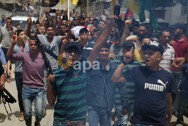 A man shouts as he holds a weapon during the funeral of Palestinian Ahmed Qutoosh, 23, who died of his wounds endured during clashes with Israeli troops in a tent city protest where Palestinians demand the right to return to their homeland at the Israel-Gaza border, in Nuseirat, in the central Gaza Strip, on May 25, 2018. Photo by Ashraf Amra