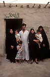 Marsh Arabs. Southern Iraq. Circa 1985. Marsh Arab man and three wives and children outside their adobe home banks of river Tigris. Polygamous family group community.