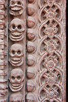 Kathmandu, Nepal.  Skulls in Carved Door Frame of the Kumari Bahal, house of the Kumari Devi, a Young Girl Revered as a Goddess by the Hindus of Kathmandu.  The door frame is of sal wood, shorea robusta.