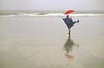 Cate 1998, Woman dancing on moody rainy beach with red umbrella and blue poncho.