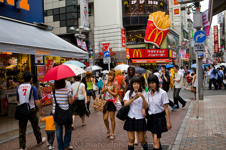 Teenage girls in school uniforms use a cell phone on a busy street characteristic of the fast paced life of Shibuya District, Tokyo, Japan.