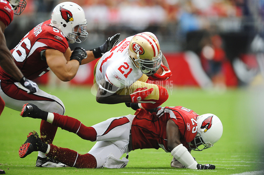 Sept. 13, 2009; Glendale, AZ, USA; San Francisco 49ers running back (21) Frank Gore gets upended by Arizona Cardinals defenders in the first half at University of Phoenix Stadium. San Francisco defeated Arizona 20-16. Mandatory Credit: Mark J. Rebilas-
