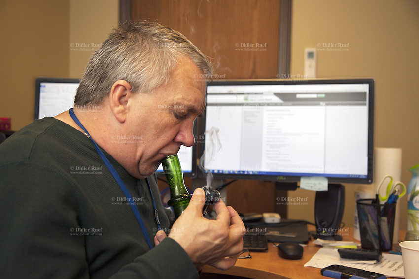 USA. Washington state. Seattle. Ben Smith is the Director of Operations at Uncle Ike's. Ben Smith is smoking a marijuana bong in his office. Uncle Ike's is authorized, according to cannabis legalization in Washington State, to sell marijuana as a retail store front. Uncle Ike's carries a wide variety of cannabis flowers, edibles, and concentrates for recreational marijuana. Cannabis, commonly known as marijuana, is a preparation of the Cannabis plant intended for use as a psychoactive drug and as medicine. Pharmacologically, the principal psychoactive constituent of cannabis is tetrahydrocannabinol (THC); it is one of 483 known compounds in the plant, including at least 84 other cannabinoids, such as cannabidiol (CBD), cannabinol (CBN), tetrahydrocannabivarin (THCV), and cannabigerol (CBG). 13.12.2014 © 2014 Didier Ruef