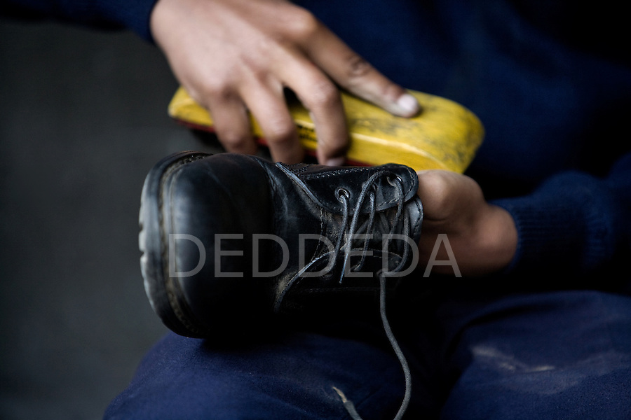 A young boy shines shoes as he gets ready for school at an orphange in Pokhara, Nepal.