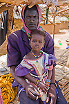 Yusufi, a young Fulani man in the tiny village of Bele Kwara, Niger, sits on a millet stalk bed with his daughter on his lap.  Yusufi sports the traditional facial scarring, that is considered beautiful. The scarring is done with a razor blade, and charcoal powder mixed with cream is rubbed into the fresh wound to create the darkened effect.