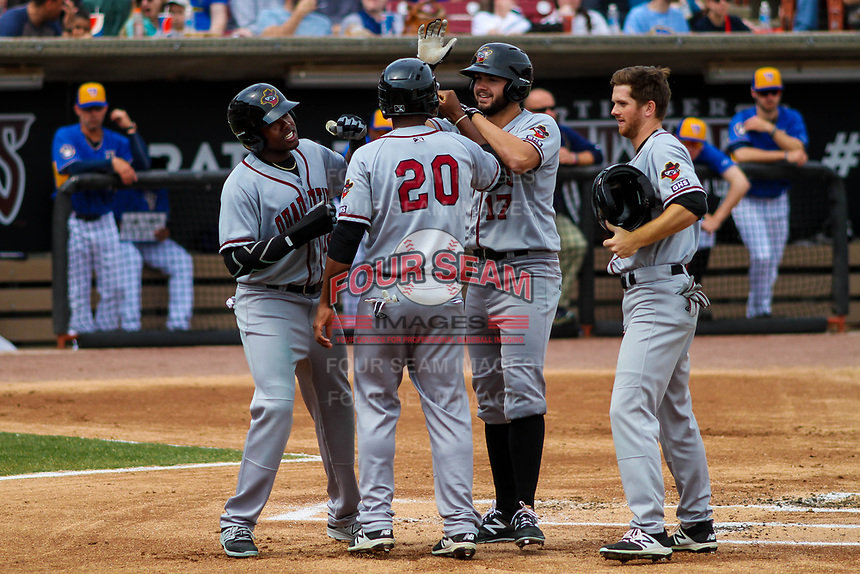Quad Cities River Bandits outfielder Ronnie Dawson (12), catcher Chuckie Robinson (20), infielder Spencer Johnson (17) and outfielder Stephen Wrenn (22) celebrate a grand slam by Johnson during a Midwest League game against the Wisconsin Timber Rattlers on April 9, 2017 at Fox Cities Stadium in Appleton, Wisconsin.  Quad Cities defeated Wisconsin 17-11. (Brad Krause/Four Seam Images)