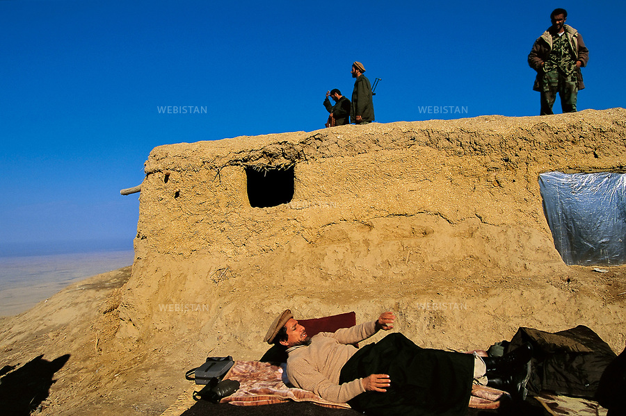 Afghanistan. Takhar. Dasht-e Qal'eh. November 2000. Seated with his bodyguards in front of Shafagh position's bunker, Commandant Massoud prepares the offensive. Afternoon nap in front of the bunker. <br /> <br /> <br /> Afghanistan. Takhar. Dasht-e Ghala. Novembre 2000.<br /> Massoud, assis devant le bunker de la position de Shafagh, avec ses gardes du corps, pr&Egrave;parant l'offensive.<br /> Sieste devant le bunker.