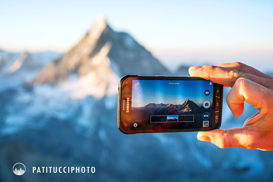 A climber stops to take a photo of the Matterhorn with his phone, Switzerland.