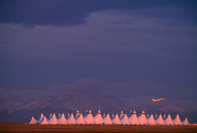 Sunrise light on Front Range with a plane taking off from DIA (Denver International Airport) in foreground, CO