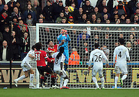 SWANSEA, WALES - FEBRUARY 21: Goalkeeper Lukasz Fabianski of Swansea punches the ball away from a Manchester United shot during the Barclays Premier League match between Swansea City and Manchester United at Liberty Stadium on February 21, 2015 in Swansea, Wales.