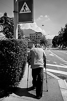 Switzerland. Canton Ticino. Viganello.An old man walks on the sidewalk. He needs to crutches to help him walking. A roadsigns for a pedestrian crossing. Viganello is a quarter of the city of Lugano. 6.07.2020  © 2020 Didier Ruef