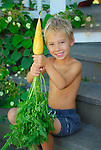 Boy on steps with large carrot