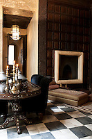A fireplace is set into the wood panelled wall of the dining room at the Riad Dar Darma which also has a dramatic black and white tiled floor