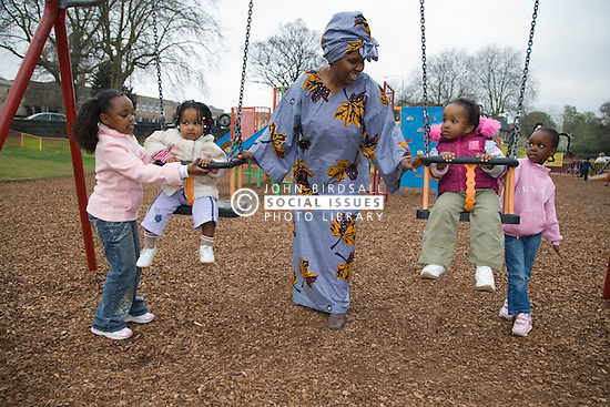 Woman playing with her four children in the playground,