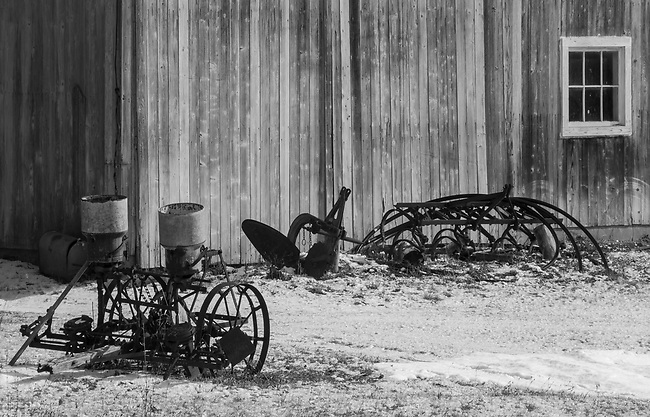 Old farm implements populate a storage area next to a barn in Door County, Wisconsin