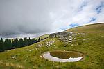 Karst rocks and tarn, Alps, Italy