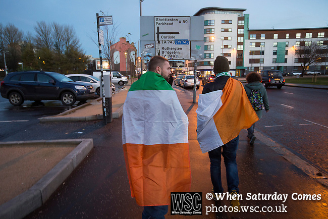 Scotland 1 Republic of Ireland 0, 14/11/2014. Celtic Park, European Championship qualifying. Two Republic of Ireland football fans draped in flags, pictured walking through the Gallowgate towards the stadium before the European Championship qualifying match against Scotland at the city's Celtic Park. Scotland won the match by one goal to nil, scored by Shaun Maloney 16 minutes from time. The match was watched by 55,000 at Celtic Park, the venue chosen to host the match due to Hampden Park's unavailability following the 2014 Commonwealth Games. Photo by Colin McPherson.