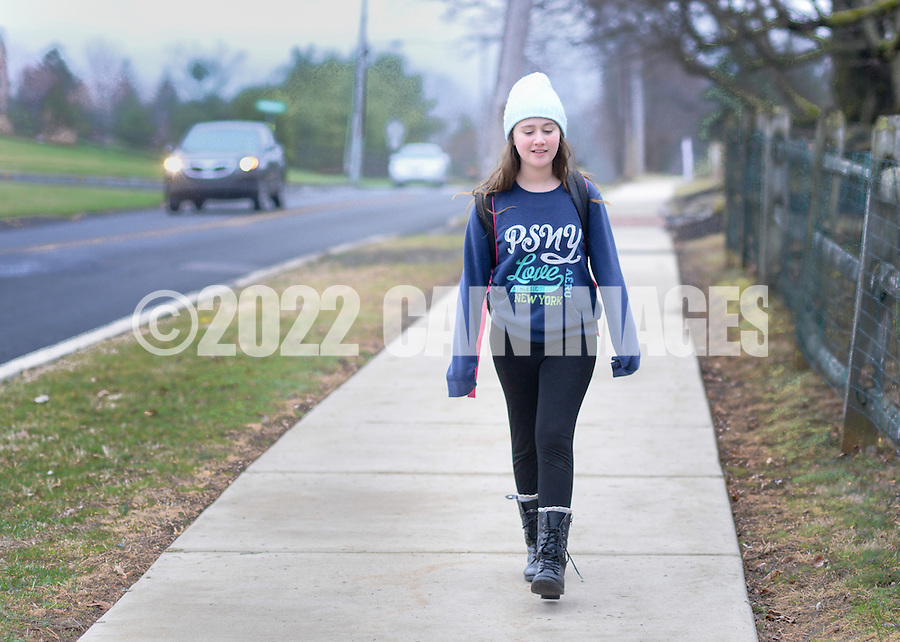 Brielle Eskolsky, 9, walks along Burnt House Hill Rd. on near Gayman Elementary School Thursday April 9, 2015 in Doylestown, Pennsylvania. Parents are concerned about a proposed parking lot plan at the school that will be revised to separate parents and school buses during drop-off times. (Photo by William Thomas Cain/Cain Images)