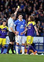 Pictured: Jose Canas of Swansea (R) sees a yellow card by match refereeKevin Friend (L).  Sunday 16 February 2014<br />