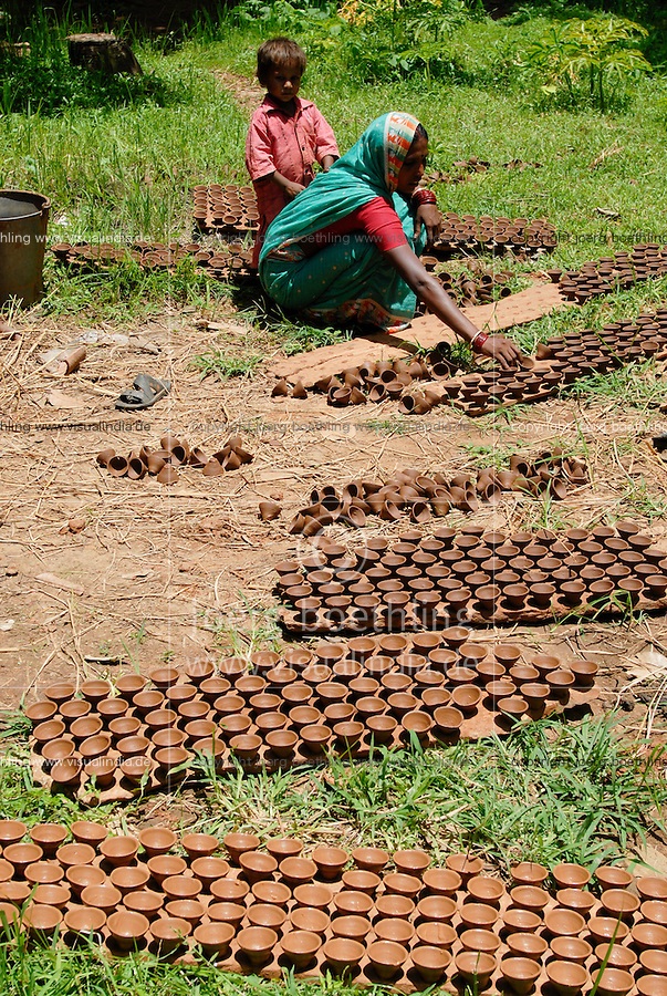 INDIA, Jharkhand, Sarwan, village Bhatkundi, potter makes one-way tea cups from clay, which are used for chai, woman dry cups in the sun / INDIEN Jharkand , Sarwan, Dorf Bhatkundi, Toepfer stellt Einweg Teetassen aus Ton her, Frau trocknet Teetassen in der Sonne