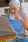 Mature woman reading newspaper