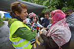 A Czech volunteer, in the yellow vest, holds 18-month old Mahdi as her mother watches. The mother and daughter, refugees from iraq, are approaching the border into Croatia near the Serbian village of Berkasovo. Hundreds of thousands of refugees and migrants from Syria, Iraq and other countries have flowed through Serbia in 2015, on their way to western Europe.