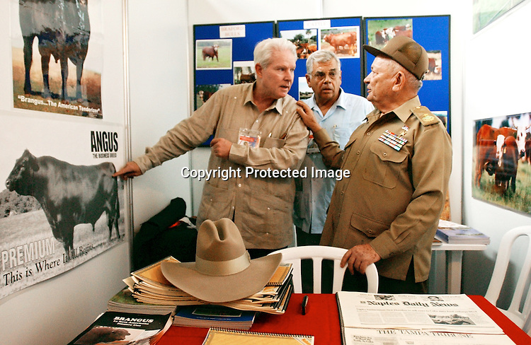 Cuba Trip.Scanned 11/21/2003.Erik Kellar/Staff..TALKING BULLS.Naples resident J. Parke Wright, left, with Rodolfo Gil, center, talks to Comandante Guillermo GarcÌa Frias during the 21st annual Havana International Trade Fair about the kinds of beef cattle Wright will soon ship to Cuba. The governmental corporation GarcÌa Frias heads oversees the plants and animals of Cuba. When it shipped 148 cows from Jacksonville in August, WrightÕs company was the first to export dairy cattle to Cuba from the United States in 40 years. Erik Kellar/Naples Daily News.