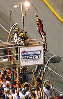 NASCAR Nextel Sprint Cup Series racer Tony Stewart stands atop the flag tower after climbing the fence surrounding the track at Daytona International Speedway to celebrate is victory in the Pepsi 400 in Daytona Beach, Fl. (Rick Wilson/The Florida Times-Union)