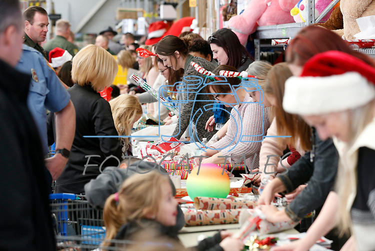 Volunteers wrap gifts at the 15th annual Holiday with a Hero program at Walmart in Carson City, on Wednesday, Dec. 19, 2018. The program pairs 240 K-8 students from the Carson City School District&rsquo;s McKinney-Vento program with first responders for a $100 Christmas shopping spree.<br /> Photo by Cathleen Allison/Nevada Momentum