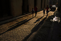 HAVANA, CUBA - JUNE 17: Shadows stretch out as parents walk their children along a cobblestoned street in Old Havana, on 17th June, 2015 in Havana, Cuba. <br /> Daniel Berehulak for Panasonic/Lumix