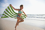 USA, Florida, St. Pete Beach, girl (8-9) running with towel on beach