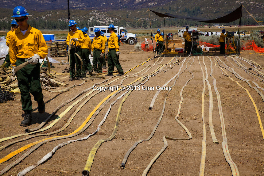 The California Conservation Corps winds up fire hoses after being used fighting the Mountain Center fire