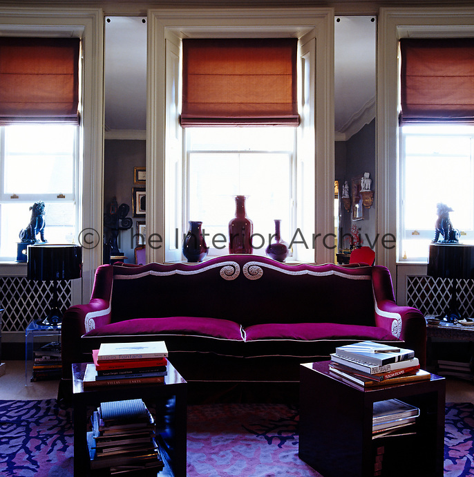 Behind the purple velvet sofa in the living room full-length mirrors between the three large windows create an illusion of space and light