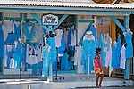 Street scene of the outside of a blue dress shop in Sainte Anne with a girl walking in dressed in bright pink