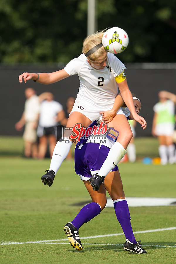 Riley Ridgik (2) of the Wake Forest Demon Deacons heads the ball away from a James Madison defender during first half action at Spry Soccer Stadium on August 29, 2014 in Winston-Salem, North Carolina.  The Dukes defeated the Demon Deacons 2-1.   (Brian Westerholt/Sports On Film)