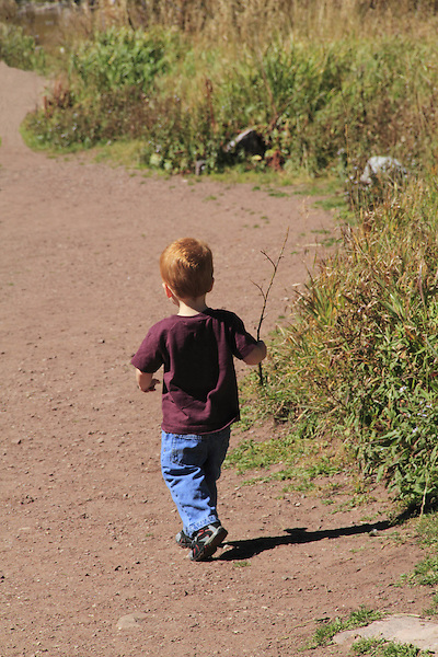 Young boy with red hair walking in a park in Boulder, Colorado, USA .  John offers private photo tours in Denver, Boulder and throughout Colorado. Year-round Colorado photo tours.