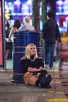 Saturday  17 December 2016<br /> Pictured: A woman Sits on the street on Swansea's Wind Street <br /> Re: Swansea City Centre and the notorious Wind street, often nicknamed 'Wine Street' is packed full of Christmas jumpers and glitzy dresses as thousands head to office dos across the UK in the biggest party night of the year.