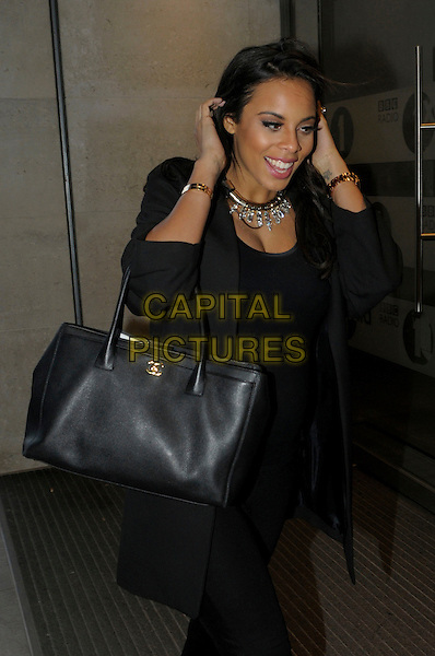 Rochelle Wiseman.The Saturdays arriving at BBC Radio 1, London, England..4th March 2013.half length black top jacket chanel bag purse pregnant necklace hands arms tattoo.CAP/IA.©Ian Allis/Capital Pictures.