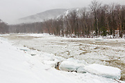 Ice flowing down the East Branch of the Pemigewasset River in Lincoln, New Hampshire during a rainy and snowy winter day.