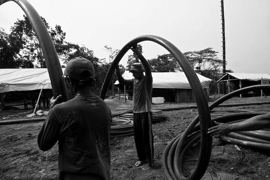 Gold miners starting operation of hydraulic mining, a form of mining that uses high-pressure jets of water to dislodge rock material or move sediment. Agua Branca gold mining village, Amazon rain forest, Para State, Brazil.
